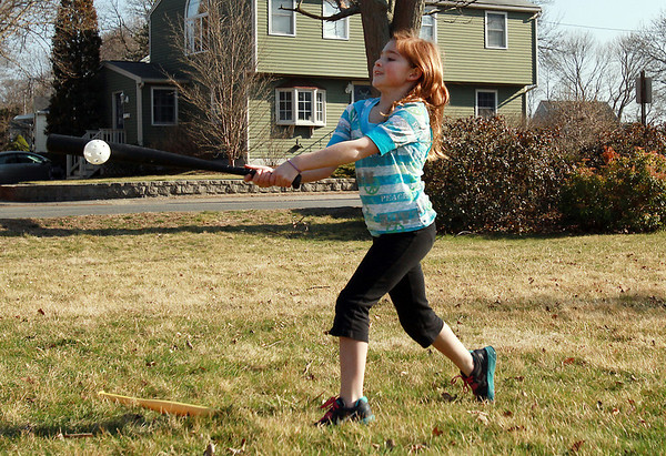Emily Gorman, 8, of Beverly, plays whiffle ball with her family on the lawn of Temple B'nai Abraham on East Lothrop St. on a warm March afternoon. David Le/Staff Photo