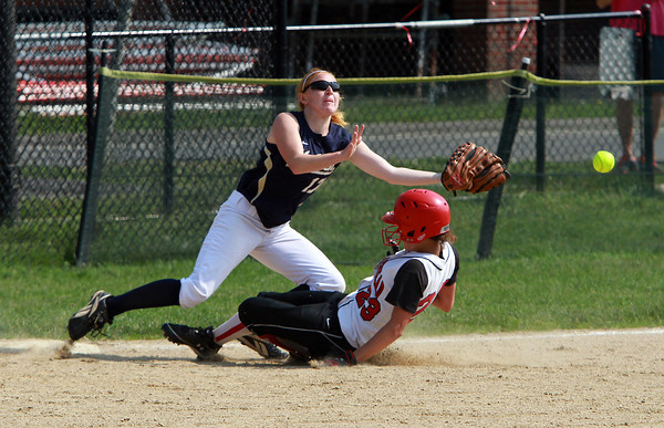 Marblehead left fielder Olivia Vener, right, slides hard into third base and causes an errant throw as the ball sails past Malden left fielder Erika Hanson, who was covering the base. David Le/Staff Photo