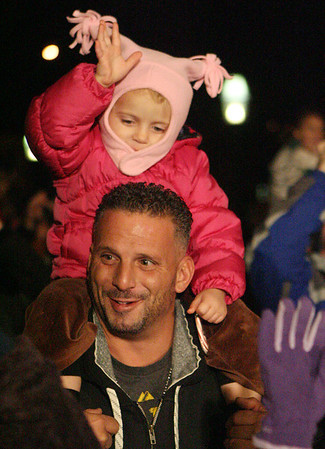 Sophia Balducci,l 3, of Salem sits on her father Frank Balducci's shoulders while waving to Santa Claus. David Le/Salem News