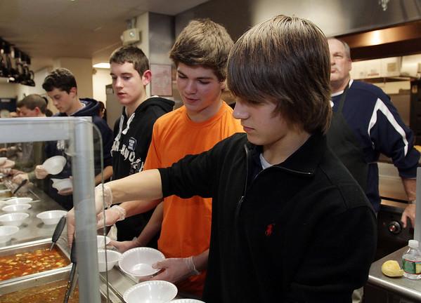 St. John's Prep sophomores Zack Pearce, left, Max Massaro, center, and Athamasi Kourkoulis, right, serve soup at St. John's Prep's Empty Bowls Dinner Party on Thursday night. David Le/Salem News