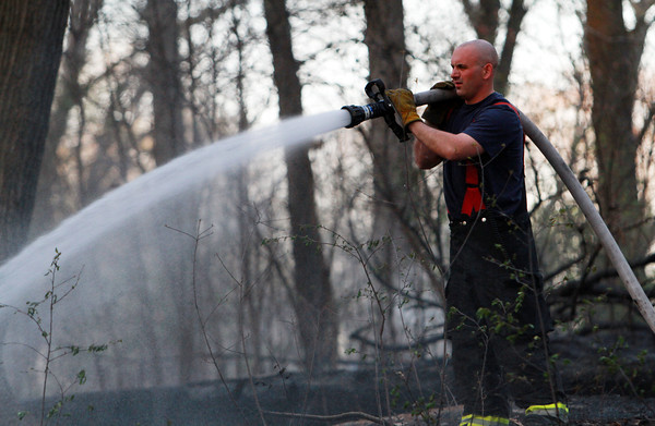 Danvers Fire Captain Adam Strohm works to extinguish a brush fire which started late Friday afternoon in the woods behind Danvers High School. David Le/Staff Photo