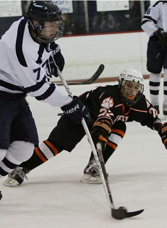 Beverly sophomore Connor Irving (22) right, attacks the puck as Peabody's Pat Ruotolo (7) left, carries it up ice. David Le/Staff Photo