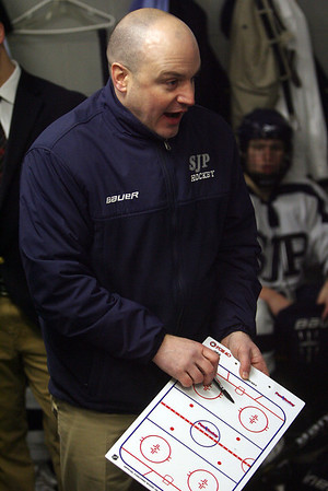 St. John's Prep head coach Kristian Hanson uses a whiteboard to show his team needed adjustments during the first intermission. David Le/Salem News