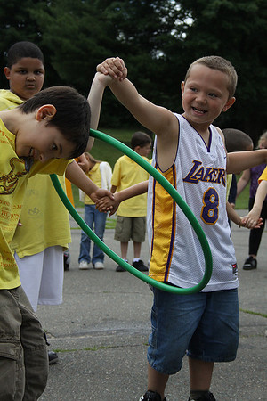 Peabody: First Graders, Peter Nocci, left, and Louis Cortez, right, pass the hula hoop to win the hula-relay as fellow classmate Samuel Olivera watches. The Welch School in Peabody held their school-wide field day on Friday, with help from the Peabody Parks and Rec Department. Photo by David Le/Salem News