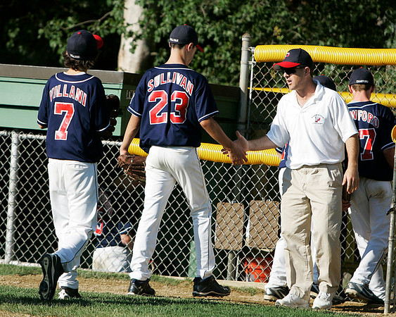 Norwood: Peabody West Coach Steve Guttadauro waits to greet starting pitcher Bobby Sullivan after he threw a scoreless 5th, and third baseman John Villani who was a human vacuum over at third the entire game. Peabody West beat Newton West 5-1 in the opening game of the Massachusetts Final Four Little League Championship Thursday afternoon at Kelly Field in Norwood. Photo by David Le/Salem News