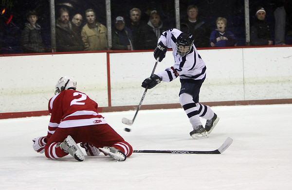 Peabody's Andrew Bisconti, right, snaps a shot past a diving Saugus player on Wednesday night. David Le/Salem News