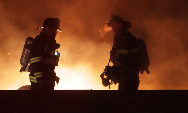 A couple of firefighters work on the roof of a burning apartment complex in the frigid temperatures on Wednesday night. David Le/Salem News
