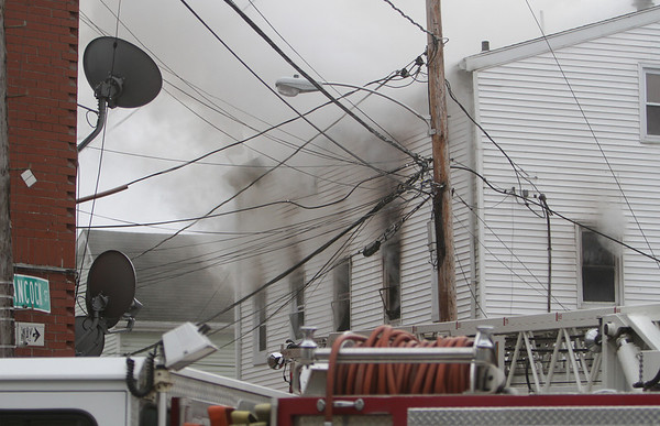 Peabody: Smoke billows out of the second and third floor windows at 5 Hancock St. in Peabody on Friday afternoon.  David Le/Salem News