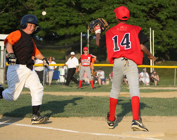 Gloucester: Beverly East catcher Shawn Perry tries to beat out a throw while Salem American firstbaseman Ronnie Baez stretches for the ball. Beverly and Salem kicked off the all-star tournament with their game on Friday evening. Photo by David Le/Salem News