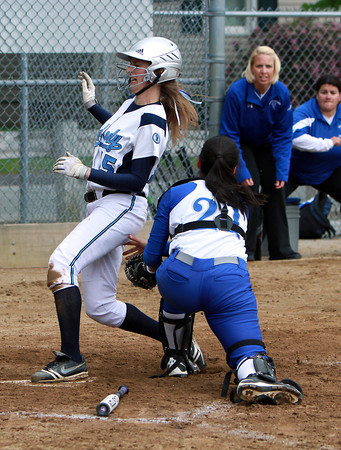 Peabody's Jess Raymond, left, manages to sneak in and touch home plate before Danvers catcher Samantha DiBella, right, can apply a tag.  David Le/Staff Photo