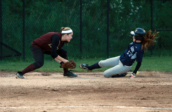 Swampscott senior Kelly Birchmore, right, slides safely into third base as the ball skips past Newburyport third baseman Maddy Stanton on Tuesday evening.David Le/Staff Photo