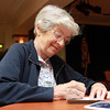 Brooksby Village resident Ginny Shedd writes a holiday card for a soldier Saturday morning at Brooksby Village when residents and volunteers helped Operation Troop Support wrap presents and write cards. David Le/Staff Photo