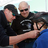 Michael Coughlin, left, of Beverly Hospital, fits Adam Poretsky, 4, of Peabody, as his grandfather Butch Ouellette, center, of Danvers looks on. The Kiwanis Club and Beverly Hospital joined forces to raise awareness for bicycle-related injuries. There was a skills course, bike and helmet fittings, safety testing stations and free bike helmets for participating. David Le/Staff Photo