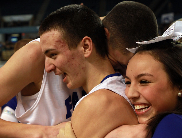 Danvers seniors Jon Amico, left, and George Merry, center, celebrate with a Danvers High Cheerleader immediately following the Falcons win over St. Joseph's on Saturday afternoon. David Le/Staff Photo