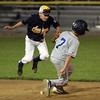 Danvers American's Matt Reidy slides safely into second base as Andover second baseman Thomas Manty leaps out of the way. David Le/Staff Photo