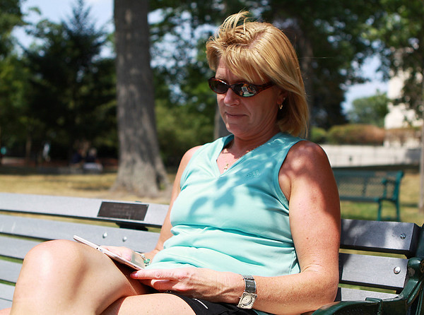 Danvers: Mary McGovern, of Groveland, enjoys a beautiful July day reading on the lawn outside the George Peabody Library in Danvers on Wednesday afternoon. Photo by David Le/Salem News