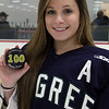 Pingree senior Lily Sabatini holds up the puck that marked her 100th point as a member of the team. Sabatini was honored before Wednesday afternoon's senior game. David Le/Staff Photo