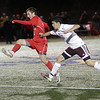 Masco's Chad Burke (2) left, manages to get a shot away while being pushed by Ludlow's Greg Santos (5) right. David Le/Salem News