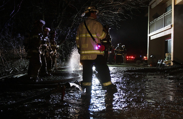 Danvers Fire Chief Kevin Farrell, right, and a few of his firefighters gaze up at the damage caused by a fire to the back of an apartment complex on Folley Pond Road on Wednesday night. David Le/Salem News