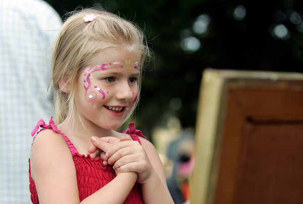 Meghan Manning, 5, of Haverhill, admires her face in a mirror after getting it painted at the Ice Scream Bowl at Salem Common on Tuesday evening. David Le/Staff Photo