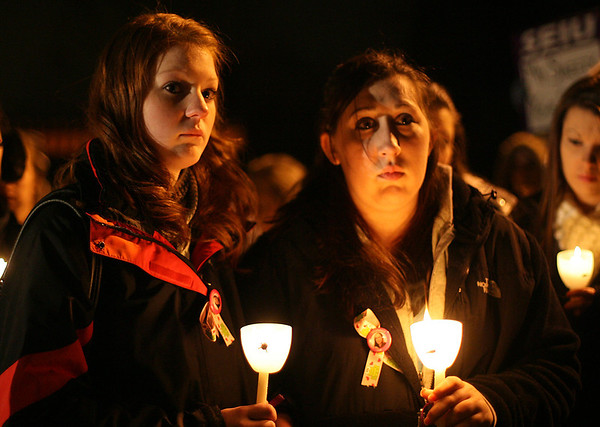 Chellsee Novack, left, and Alicia Stagnone, of Danvers, listen to speeches during a candlelight vigil for Stephanie Moulton, a human service worker who was allegedly murdered by a patient last January. David Le/Salem News