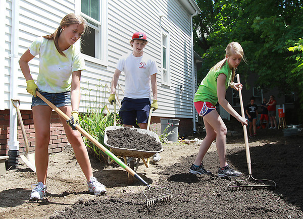 Masco sophomore Fiona Greenaway, left, and junior Katherine Dobson, right, comb over some fresh dirt delivered by junior Derek Grammer, center, while helping to clean up the outside of 23 Chase St in Beverly as part of Habitat for Humanity. David Le/Staff Photo