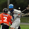 Danvers attacker Shea Doyle, right, is separated from the ball as he is checked by Beverly defenseman Ty Martz, left, on Thursday evening. David Le/Staff Photo