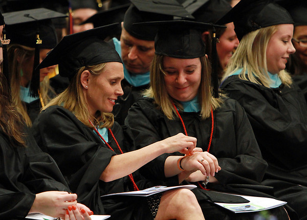Nina Miller, of Marblehead, left, helps Maria Morrissey, of Peabody, right, tie a piece of string during a greeting by Amy Everitt, President of the Salem Chapter of the Massachusetts State College Association, during the commencement ceremonies on Thursday afternoon. David Le/Staff Photo