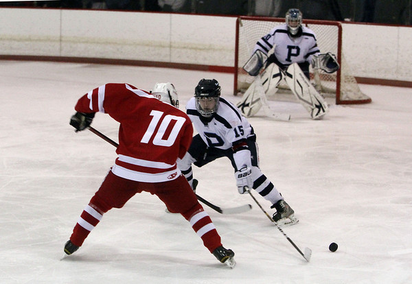 Peabody's Ryan McManus (15) right, pokes the puck away from Saugus' Drew Oxley on Wednesday night. David Le/Salem News