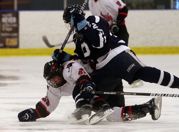 Peabody's Anthony Robinson (22) right, and Salem's Dan Tsivin (29) left, collide as they race for a loose puck on Wednesday afternoon. David Le/Salem News