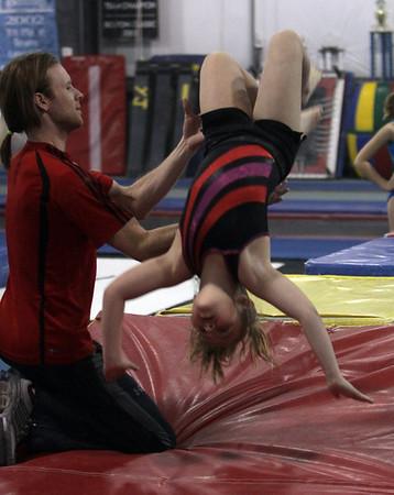 Yellowjackets gymnast instructor Tim Kormann, left, helps Katie Dumont execute a back flip. David Le/Staff Photo.