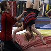 Yellowjackets gymnast instructor Tim Kormann, left, helps Katie Dumont execute a back flip. David Le/Staff Photo.