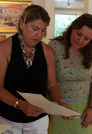 Ipswich: Pam Morss of Manchester, left, looks at some artwork on display at the silent art auction held at Wavepaint Design and Gallery in Ipswich, along with owner Barbara DiLorenzo, right. The benefits from the auction will go to Partners in Development and their work in Haiti. Photo by David Le/Salem News