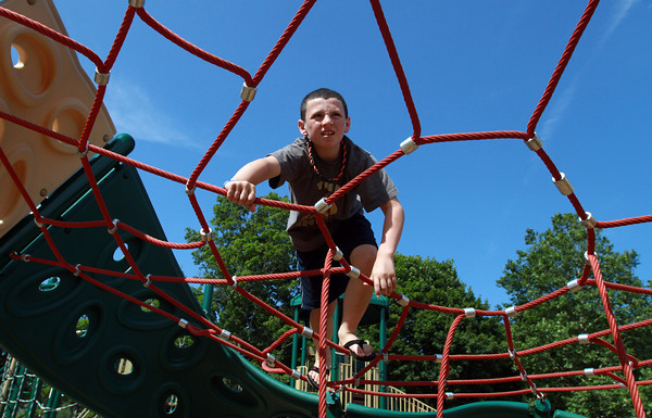 Cameron Burns, 10, of Beverly, climbs across a web at Kimball Haskell Park on Thursday afternoon. David Le/Staff Photo