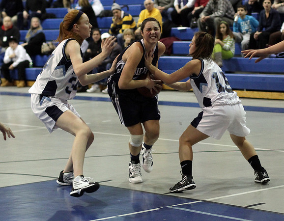Swampscott's Ara Talkov, center, drives into the paint while being pressured by Peabody's Caroly Scacchi (34) left, and Jacquelyn Goodwin (15) right. David Le/Salem News