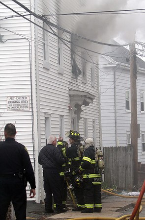 Peabody: Local firefighters discuss the next step to take in fighting a 3-alarm fire on Hancock St. on Friday afternoon. David Le/Salem News