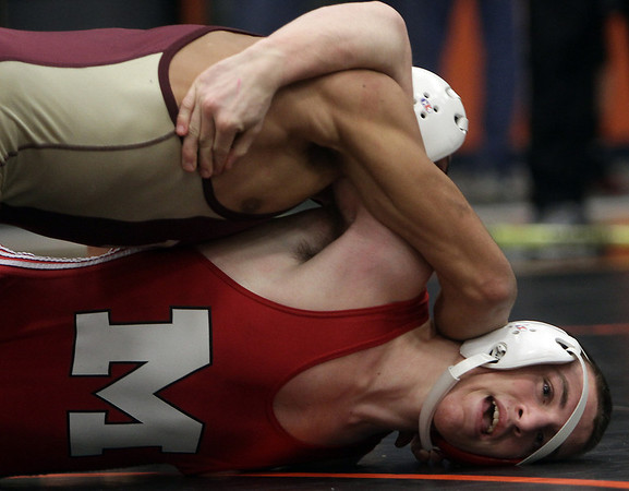 Masco's Steve Jones, bottom, tries to get out of the grasp of Whittier Tech's Travis Yell, top, during the state semifinal wrestling meet at Beverly High School on Saturday afternoon. David Le/Salem News