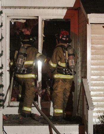 Hamilton: Firefighters prepare to enter a house on Beech St. in Hamilton which caught fire on Thursday evening. David Le/Salem News