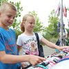 Twins Joshua and Brianna Berube, 8, look at colorful dog collars at a vendor's booth at a Fundraiser for Salem Play Areas for Canine Exercise at Leslie's Retreat Dog Park in Salem on Saturday morning. David Le/Staff Photo