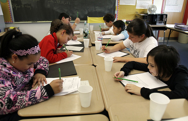 A group of 4th grade students at Bentley School in Salem work on a introductory placement excersize to see where the students should be placed for after school homework help/. David Le/Salem News