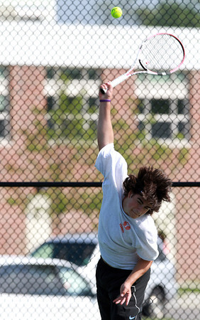 Beverly High School first singles player Josh Cronin leaps his and smashes a serve against Austin Prep on Friday afternoon. David Le/Staff Photo