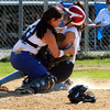 Danvers High School senior catcher Samantha DiBella tags out a sliding Dracut runner as she blocks the plate to save a run. David Le/Staff Photo