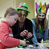 Arthur Macedo, 5, of Peabody, left, gets help making a Mardi Gras mask by Colleen Silva, 15, center, and Briana Silva, also 15, both of Peabody at St. Thomas the Apostle Church on Tuesday afternoon. David Le/Staff Photo