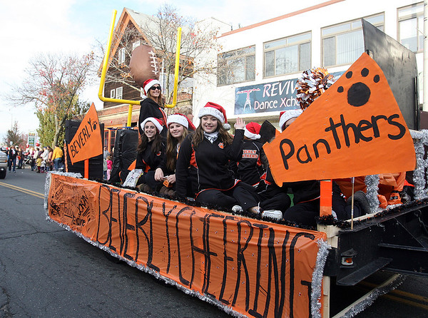 The Beverly High School Cheerleaders wave to spectators as they ride down Cabot St. David Le/Salem News
