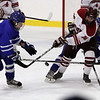 Danvers' Rob Buchanan, left, fights for the puck with Gloucester's Matt Brennan (18). David Le/Staff Photo