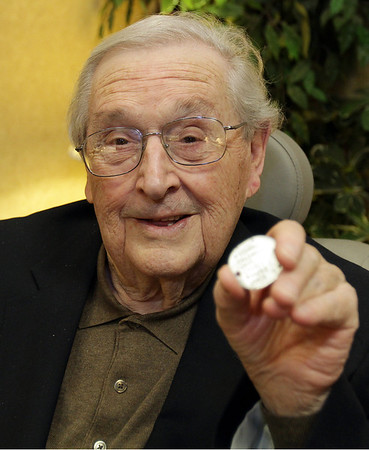Former US Marine Richard Urie holds up his dogtag from his days in service, which he lost while fighting in WWII. A farmer found his tag in a field, and recently returned the tag to its owner. David Le/Salem News