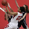 Salem's Alex Bryant (23) runs into two Swampscott defenders on her way to the hoop on Friday night. David Le/Salem News.