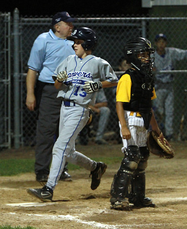 Danvers American left fielder Casey Bussone (13) crosses home plate with another run for Danvers as Saugus catcher Mason Blocke waits for the throw.