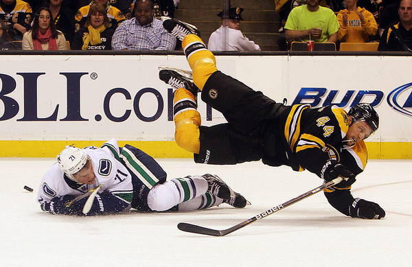 Bruins defenseman Dennis Seidenberg gets tripped and goes airborne by a sliding Mason Raymond. David Le/Salem News