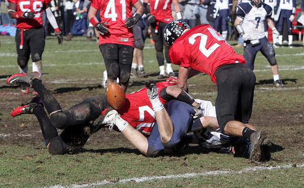 Swampscott wide receiver Nick Mennino (27) center, fumbles the football after a hit from Marblehead's Will Quigley (20) left, and Evan Rhodes (24) right. David Le/Salem News
